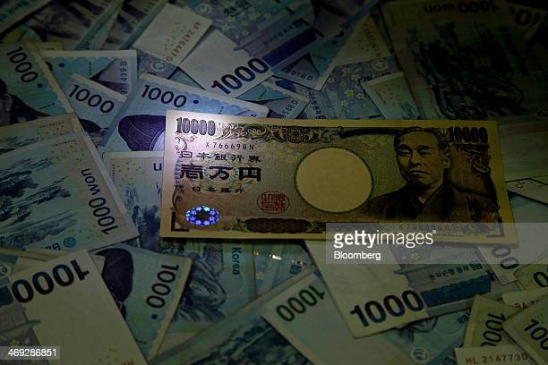 A Japanese 10000 yen banknote sits on a pile of South Korean 1000 won banknotes for a photograph at the Korea Exchange Bank headquarters in Seoul...