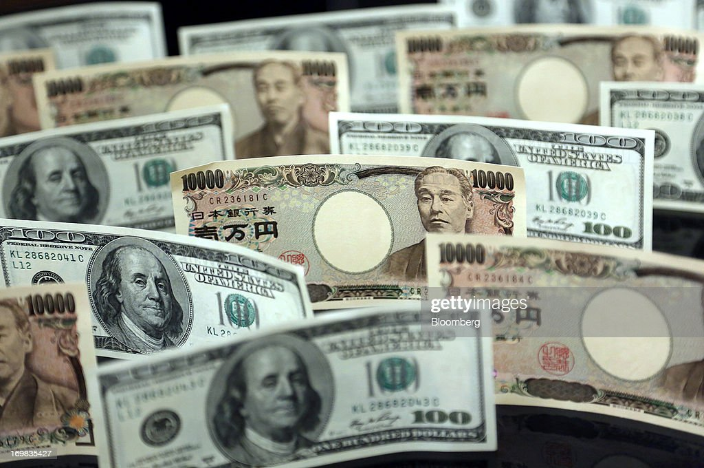 Japanese 10,000 yen banknotes and U.S. one-hundred dollar banknotes are  arranged for a photograph