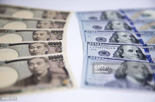 Japanese 10000 yen left and US 100 dollar banknotes are arranged for a photograph in Tokyo Japan on Tuesday Sept 5 2017 Japanese stocks fell as the...