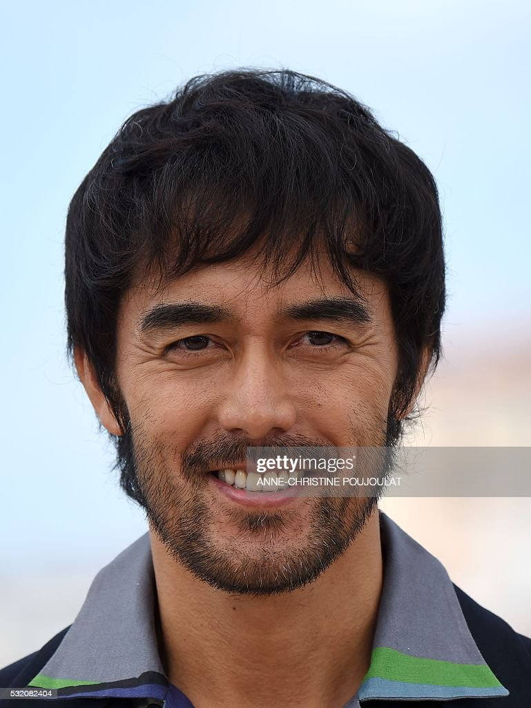 Japanese actor Abe Hiroshi smiles on May 18, 2016 during a photocall for the film 'After the Storm (Umi Yorimo Mada Fukaku)' at the 69th Cannes Film Festival in Cannes, southern France. / AFP / ANNE