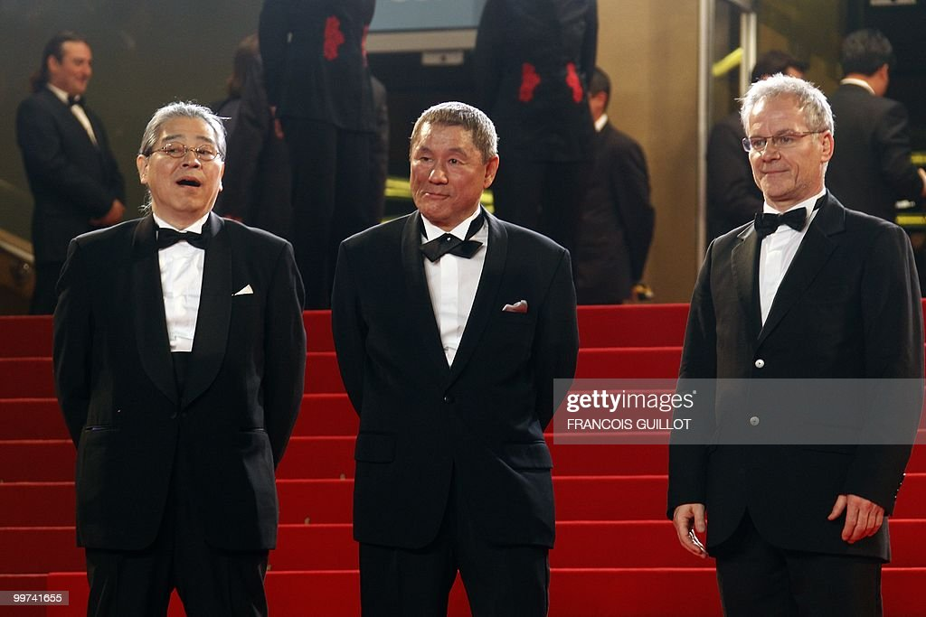 Japanese actor and director Takeshi Kitano (C) and Japanese producer Masayuki Mori (L) pose next to French director of the Cannes Film Festival Thierry Fremaux as they arrive for the screening of 'Outrage' presented in competition at the 63rd Cannes Film Festival on May 17, 2010 in Cannes.