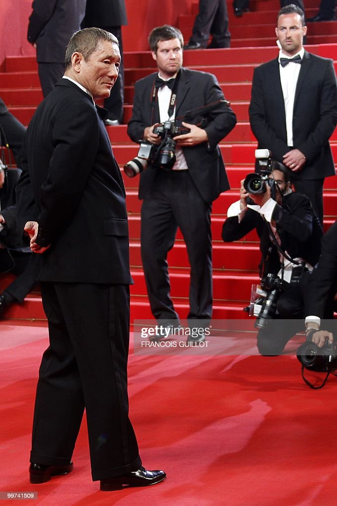Japanese actor and director Takeshi Kitano (L) arrives for the screening of 'Outrage' presented in competition at the 63rd Cannes Film Festival on May 17, 2010 in Cannes.