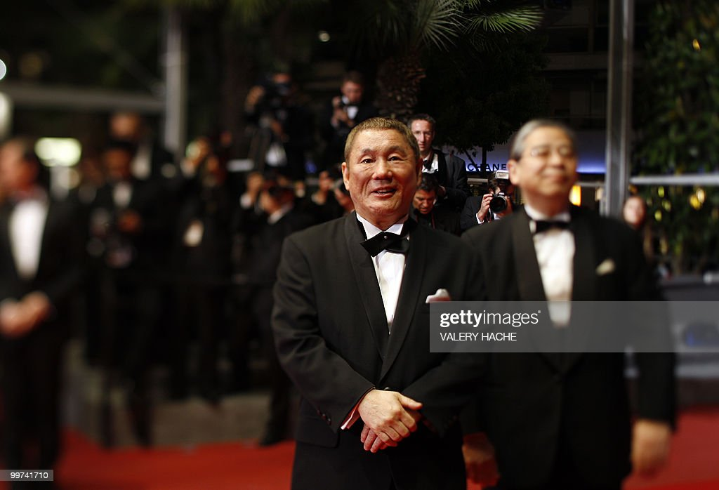 Japanese actor and director Takeshi Kitano (C) arrives for the screening of 'Outrage' presented in competition at the 63rd Cannes Film Festival on May 17, 2010 in Cannes. Photo taken with a tilt and shift lens.