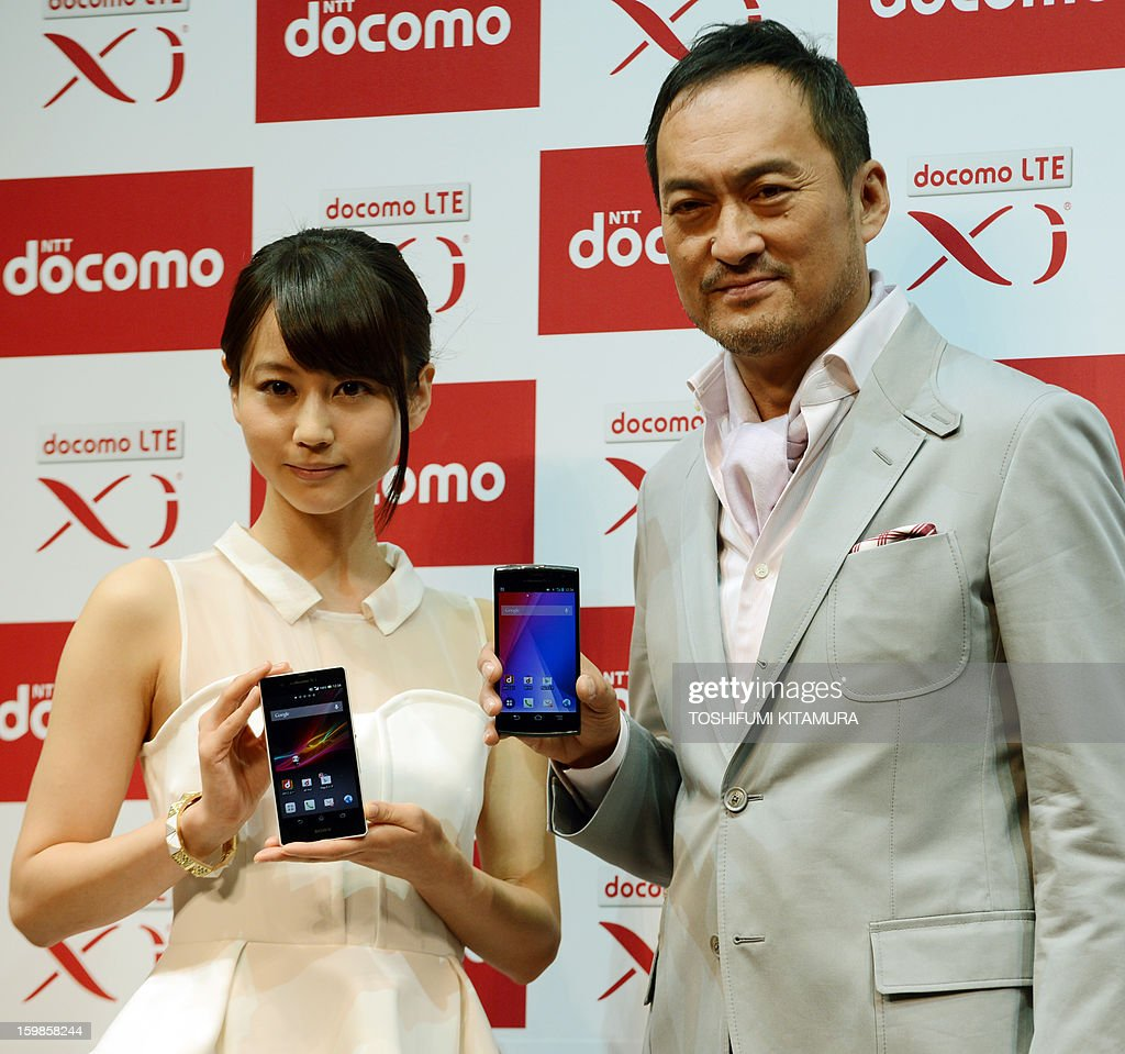 Japanese actor Ken Watanabe (R) and actress Maki Horikita (L) pose in a photo session during the NTT Docomo's 2013 Spring lineup press preview in Tokyo on January 22, 2013. The new lineup of 11 smartphones and tablets plus one mobile Wi-Fi router will launch in sequence beginning on January 25 in Japan.