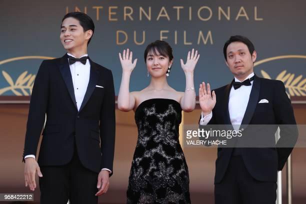 Japanese actor Masahiro Higashide Japanese actress Erika Karata and Japanese director Ryusuke Hamaguchi wave as they arrive on May 14 2018 for the...