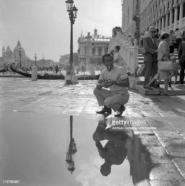 Japanese actor Toshiro Mifune holding a cinecamera on Riva Schiavoni by St Mark Square reflected crouched in a puddle smoking a cigarette Venice...
