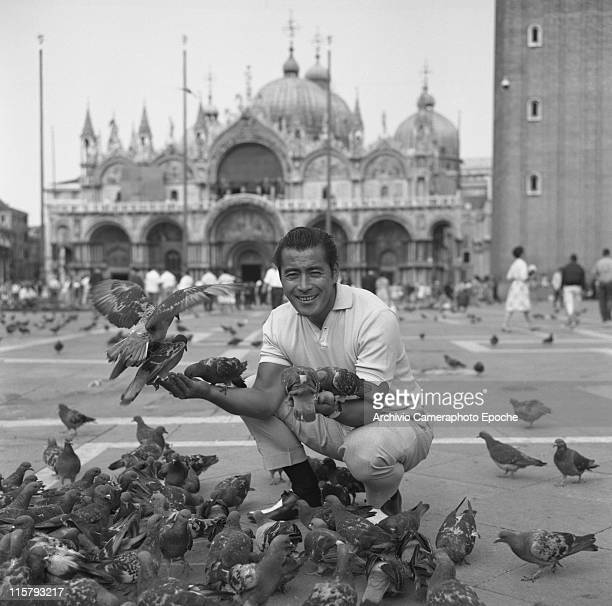 Japanese actor Toshiro Mifune smiling crouched in St Mark Square feeding pigeons and posing for the picture Venice September 1961
