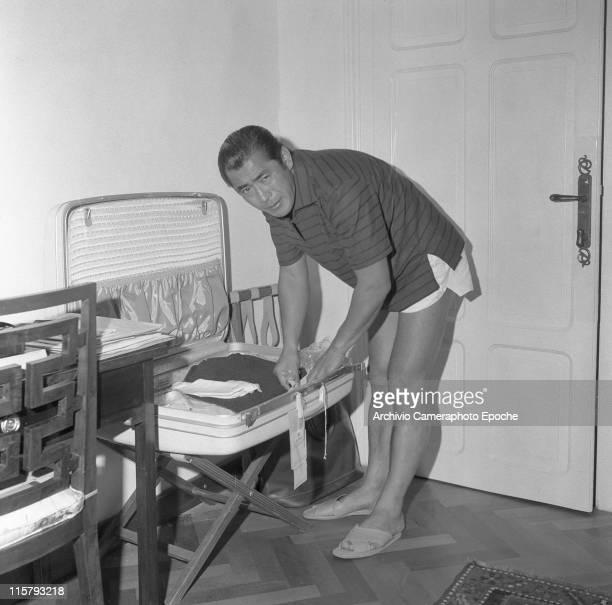 Japanese actor Toshiro Mifune wearing a striped tshirt and short trousers packing a luggage in his hotel room Venice September 1961