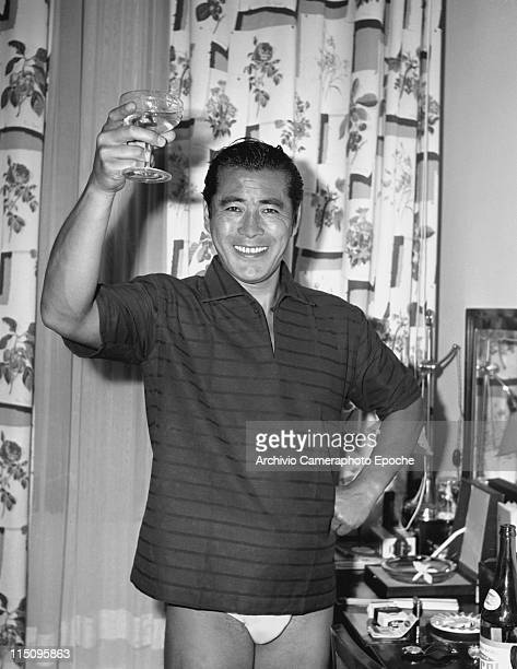 Japanese actor Toshiro Mifune wearing a striped tshirt and underpants toasting with a champagne glass with flowered curtains behind him in his hotel...