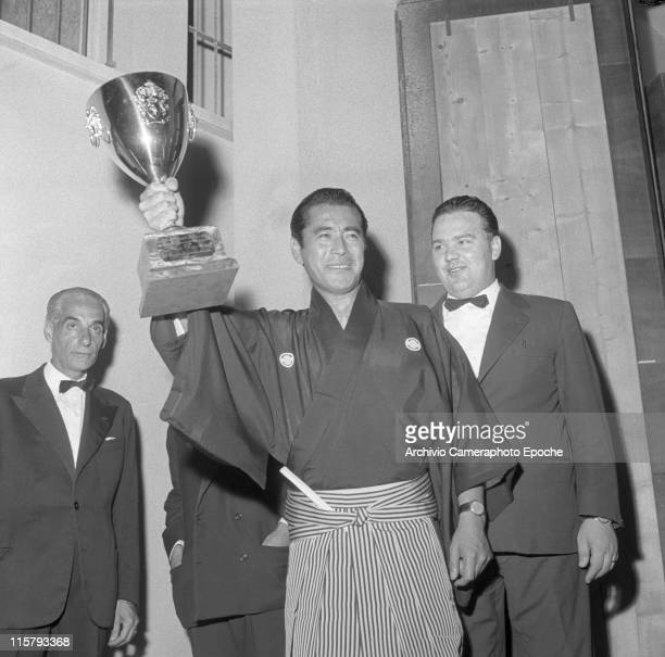 Japanese actor Toshiro Mifune wearing a traditional haori kimono with a fan in his belt lifting the Volpi Cup as best actor during the Movie Festival...