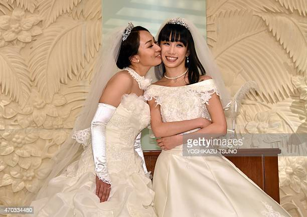 Japanese actress Akane Sugimori is kissed by her partner Ayaka Ichinose both dressed in white at a press conference after their marriage ceremony in...