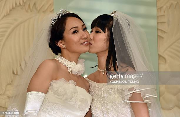 Japanese actress Akane Sugimori kisses her partner Ayaka Ichinose both dressed in white at a press conference after their marriage ceremony in Tokyo...