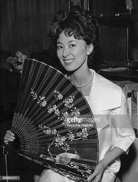 Japanese actress and writer Keiko Kishi with a fan from her collection at home in Paris France 1959