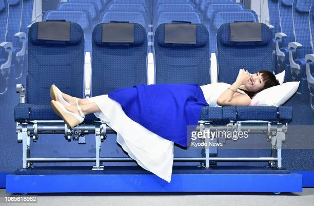 Japanese actress Haruka Ayase lies down on seats to be installed on All Nippon Airways Co's Airbus A380 at an event in Tokyo on Nov 27 2018 The...