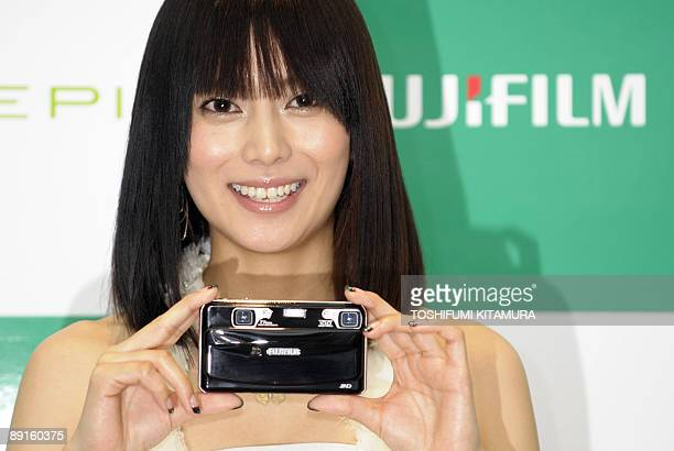 Japanese actress Ko Shibasaki holds Fujifilm's latest compact digital camera 'Finepix Real 3D W1' during its press preview at the company's...