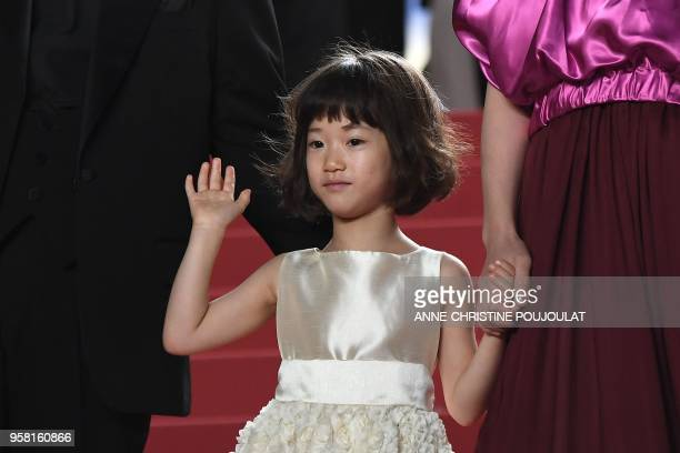 Japanese actress Miyu Sasaki waves as she arrives on May 13 2018 for the screening of the film Shoplifters at the 71st edition of the Cannes Film...