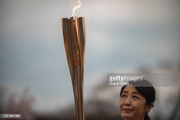 Japanese actress Momoko Kikuchi looks at the Olympic torch during a ceremony on the second day of the Tokyo 2020 Olympic Games torch relay at...