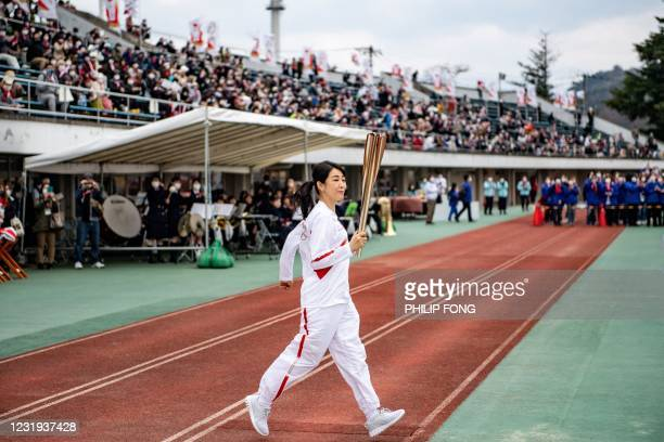 Japanese actress Momoko Kikuchi runs with the Olympic torch during a ceremony on the second day of the Tokyo 2020 Olympic Games torch relay at...