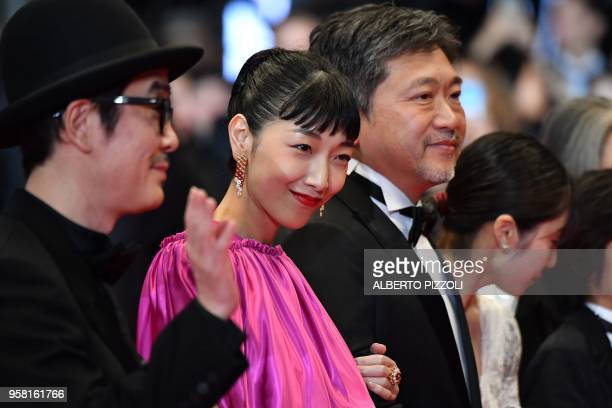 Japanese actress Sakura Ando poses with Japanese writer and actor Lily Franky and Japanese director Hirokazu KoreEda as they arrive on May 13 2018...