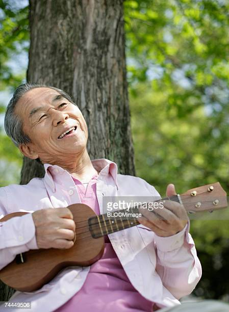 Japanese adult man playing the guitar under tree