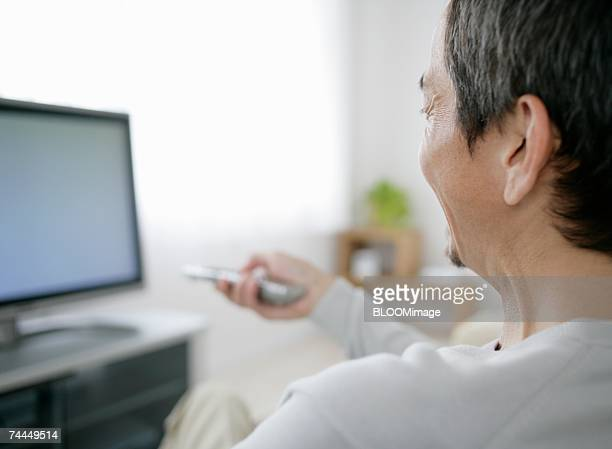 Japanese adult man using TV remote with smiling