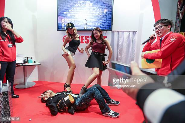Japanese adult models pose with a visitor laying on the floor during the Japan Adult Expo at the Toyosu PIT on November 17 2015 in Tokyo Japan At the...