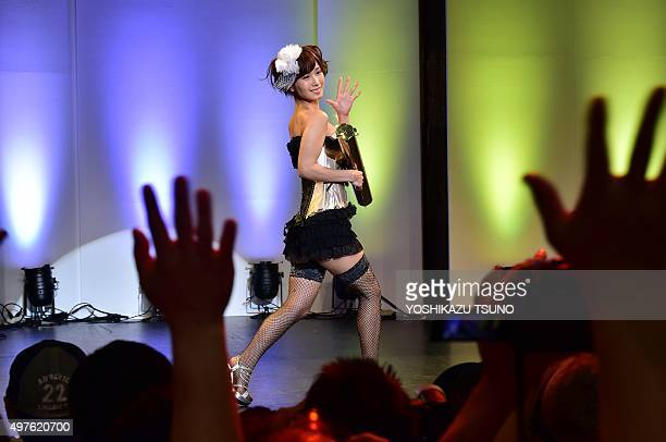 Japanese adult video actress Minami Kojima waves to her fans during a lingerie fashion show at Japan Adult Expo in Tokyo on November 18 2015...