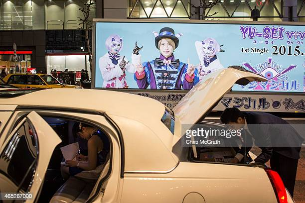 Japanese advertising truck is driven past a limosine parked at the famous Shibuya intersection on March 5 2015 in Tokyo Japan Over the past five...