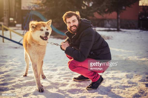 Japanese Akita dog and bearded hipster on the playground