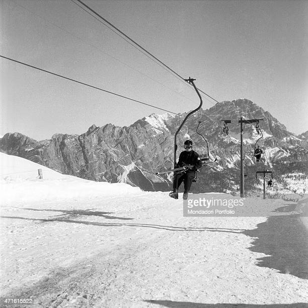 Japanese alpine ski racer Chiharu Igaya going uphill on the chairlift during the VII Olympic Winter Games Cortina d'Ampezzo 1956