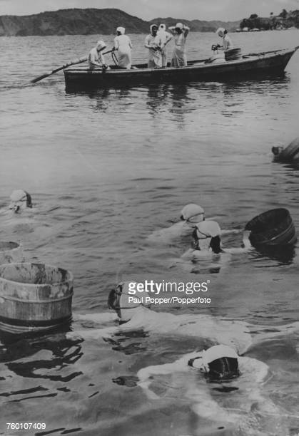 Japanese Ama pearl divers off Mikimoto Pearl Island in Ise Bay offshore Toba Mie Prefecture Japan where the women dive for cultured pearl oysters...