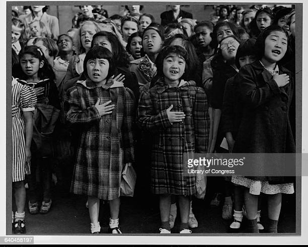 Japanese Amercian girls stand with their hands over their hearts with a group of school girls who pledge allegiance to the United States flag San...