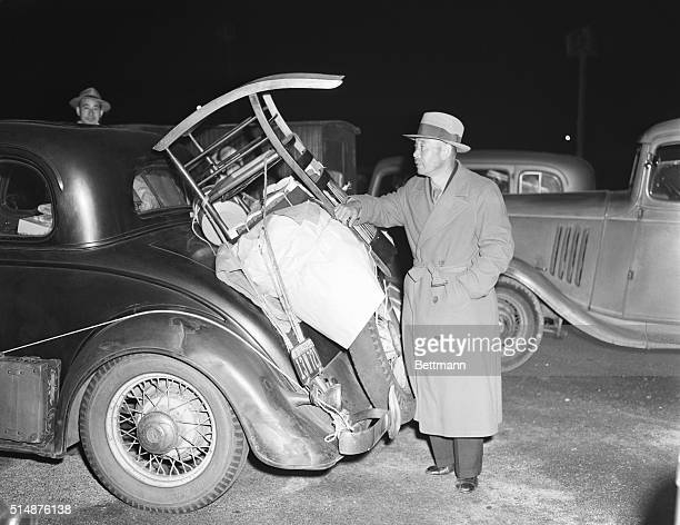 Japanese American citizen stands behind his car, packed with personal belongings, at the Rose Bowl in Pasadena, California. This car was one of 350...
