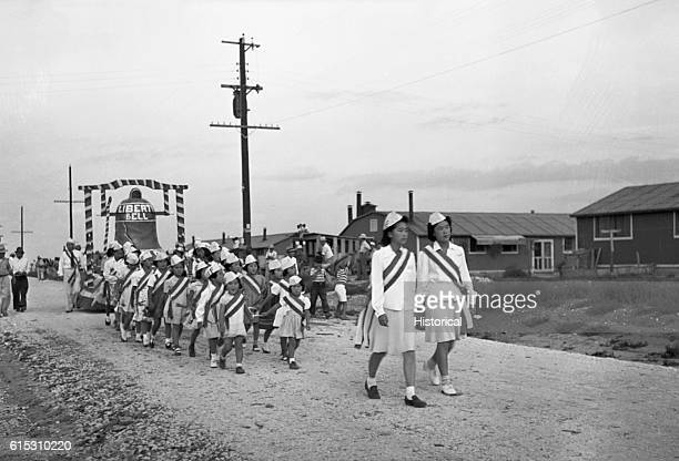Japanese American girls show their patriotism as they parade with a Liberty Bell float while being held in an internment camp | Location in an...