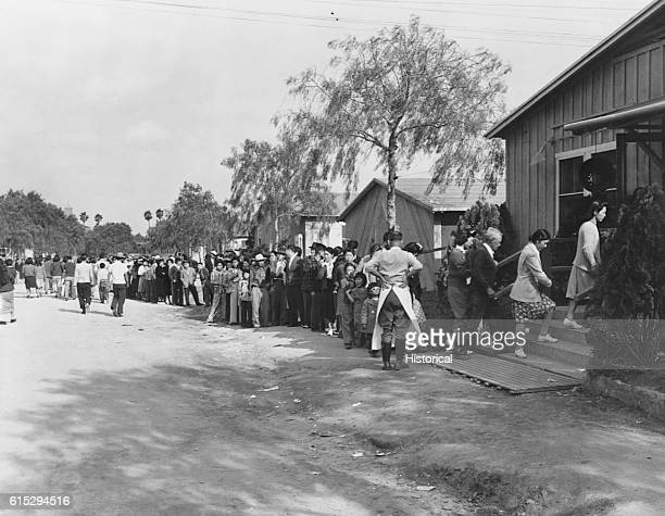 Japanese American internees wait in line for the dining hall at the Santa Anita Race Track in Arcadia California which is being used as an assembly...