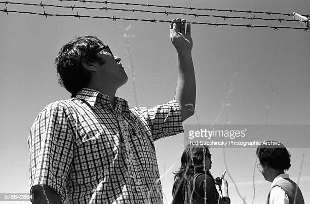 A Japanese American man touches some barbed wire at the Tule Lake Internment Camp where his parents were interned during World War Two | Location...