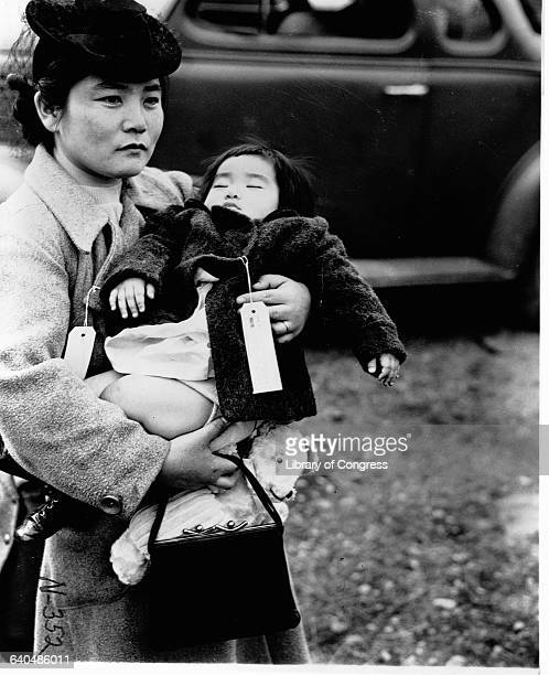 A Japanese American woman holds her sleeping daughter as they prepare to leave their home for an internment camp Bainbridge Island 1942