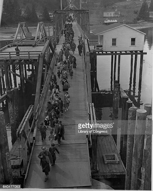 Japanese Americans escorted by soldiers cross a bridge as they are evacuated from Bainbridge Island to be taken to a relocation camp. Washington,...