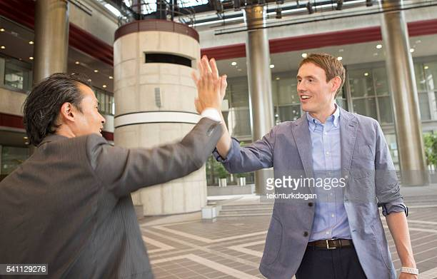 japanese and european businessmen highfive salute at kyoto japan - lypsekyo16 stock pictures, royalty-free photos & images