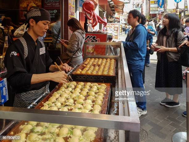 japanese and international tourists queue up to enter the donamon museum where you can eat, learn about takoyaki (famous octopus filled snack) in namba, osaka. - takoyaki stock pictures, royalty-free photos & images