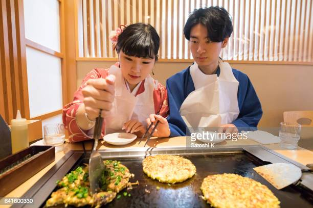 japanese and korean couple cooking okonomiyaki japanese food - okonomiyaki stock pictures, royalty-free photos & images