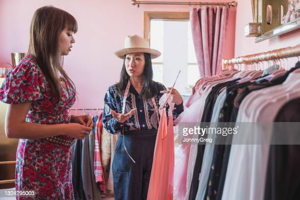 japanese and mixed race costume designers discussing garment - fashion collection stock pictures, royalty-free photos & images