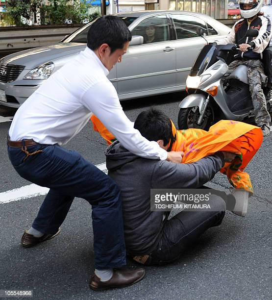 A Japanese antiChina protester scuffles with a man appearing to be a chinese resident of Japan who sat in front of an antiChina protest march in...