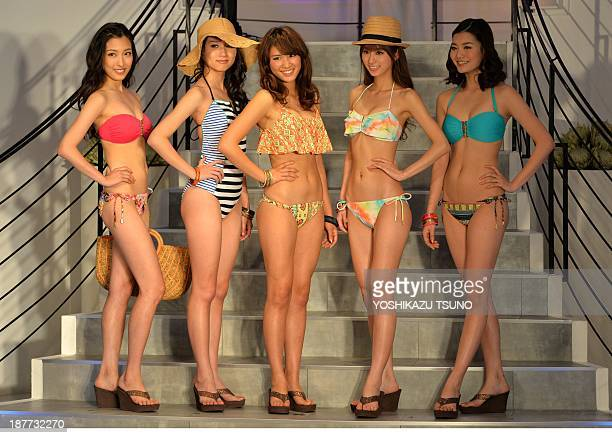 Japanese apparel maker Sanai's new campaign girl Ikumi Hisamatsu and models display their latest swimwear during Sanai's 2014 collection in Tokyo on...