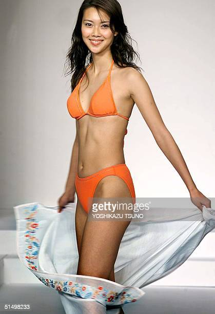 Japanese apparel maker Unichika's campaign model Emiko Koizumi displays a bikini swimsuit with a wrapped skirt during the 2000 swimwears collection...