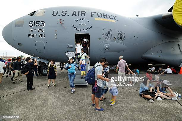 Japanese are seen near a US Aire Force Boeing C17 Globemaster displayed on the tarmac of the Yokota US air base in Tokyo Japan on September 20 2015...