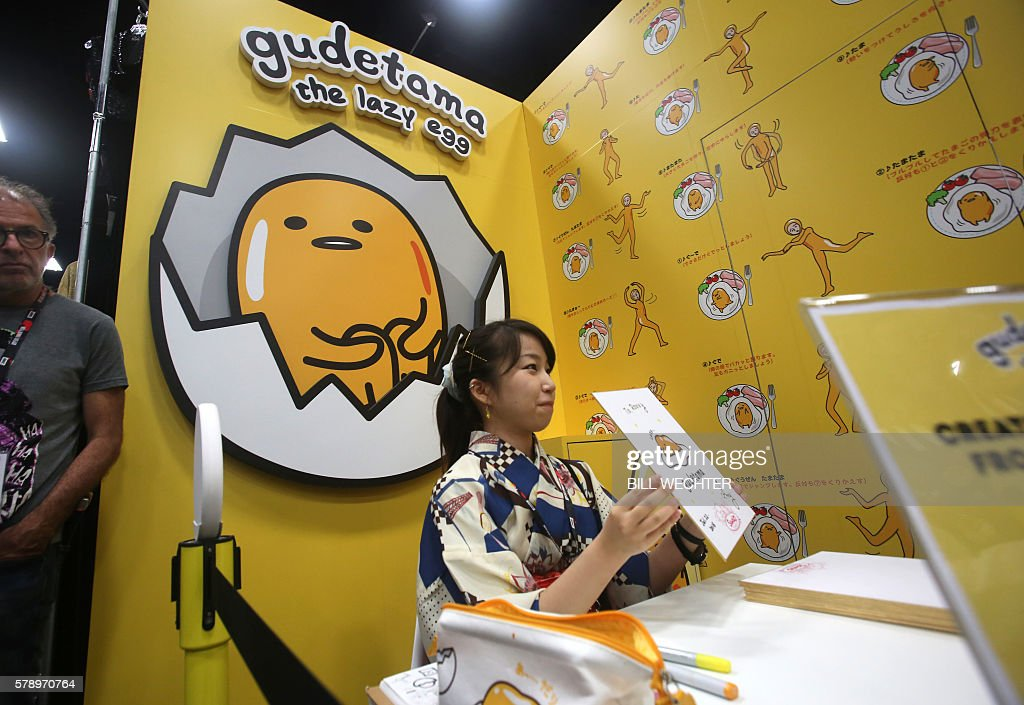 Japanese artist Amy, who draws Gudetama, the lazy egg, shows an original lazy egg drawing she just drew to give to a convention attendee, one of many she was drawing and giving away during Comic-Con International 2016 in San Diego, California, July 22, 2016. / AFP / Bill Wechter