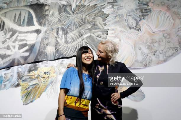 Japanese artist Maki Ohkojima poses with Frencg fashion designer Agnes Trouble aka Agnes B in front of her piece of art during the private view of...