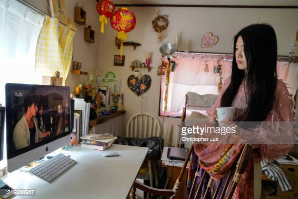 Japanese artist Mika Tamori in her home studio watches the live stream performance of Shawn Mendes and Camila Cabello during the One World Together...
