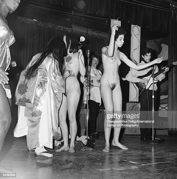 Japanese artist Yayoi Kusama wearing a kimono painting dots on a naked young woman who is dancing on stage in front of a rock band during a Body...